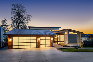 Beautiful modern style luxury home exterior at sunset with glowing interior lights. Features three...
