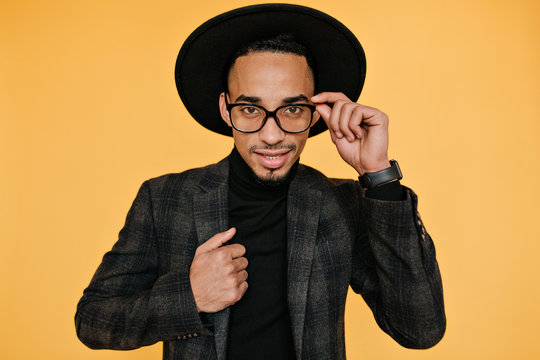 Studio portrait of handsome brown-eyed male model playfully touching his hat. Indoor photo of well-dressed african man in good mood.