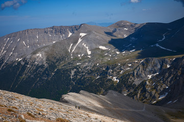 Tourists walking along a rocky trail. View of the high mountain slopes. Mountain hiking. Trekking in Mount Olympus. Greece. National Park.