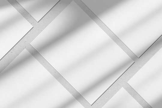 Empty white vertical rectangle poster or business card mockups with diagonal window shadow on the gray concrete wall.Flat lay, top view. For advertising, brand design, stationery presentation.