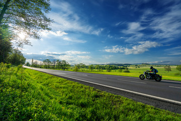 Fotobehang - Black motorcycle riding on an empty asphalt road in a rural landscape under a radiant sun and dramatic clouds