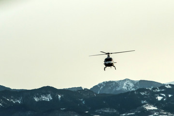 An atmospheric picture shows the helicopter climbing in front of the high snowy mountains.