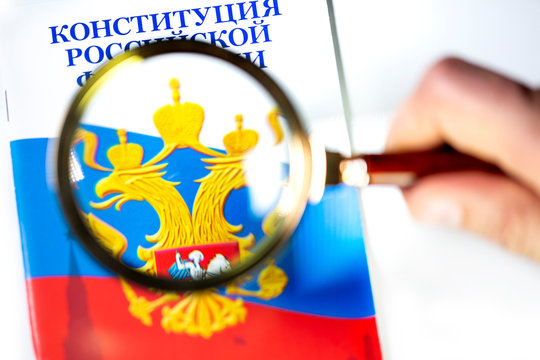 """A man studies The Constitution of the Russian Federation under a magnifying glass on white background. The Russian inscription on the photo reads """"The Constitution of the Russian Federation"""""""