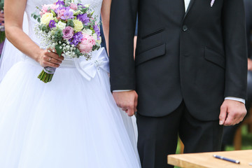 A detail picture from the wedding. The pair is holding their hands during the ceremony. A symbol of their love.