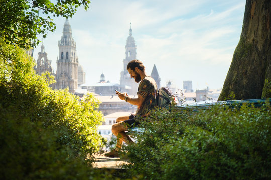 Young Man On Pilgrimage At Santiago De Compostela With Phone