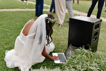 Beautiful bride is turning on music on the laptop outdoors on the grass on the wedding celebration