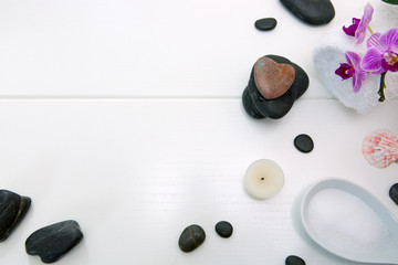 Spa setting with pink orchids , black stones and candle on white wood background.