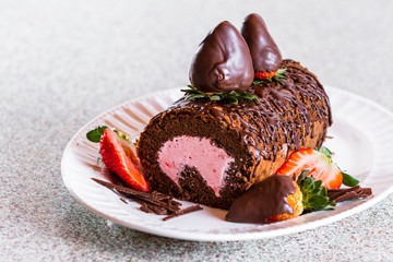 Chocolate log cake rolled with strawberry mouse