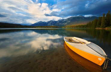 Beautiful sunset over Edith Lake with a yellow boat in foreground, Jasper National Park, Alberta, Canada