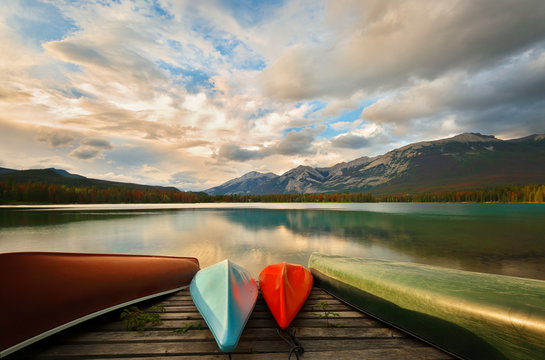 Beautiful sunrise over Edith Lake with  colorful boats in foreground, Jasper National Park, Alberta, Canada