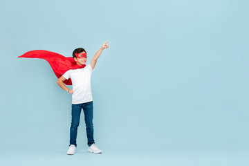 Smiling superhero boy in red mask and cape pointing hand aside