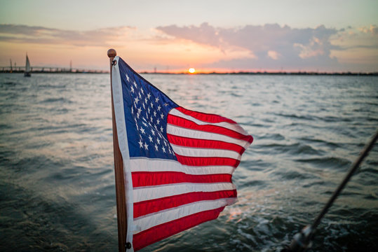 American flag flies from transom of sailboat with sunset in background in Galveston Bay Texas