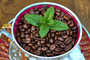 Vintage coffee cup with coffee beans and mint leaves
