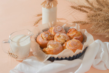 Food, pastry, baking. Freshly baked homemade snail buns with milk in a jug and a glass bottle. Balanced nutrition, proteins and carbohydrates, cereals