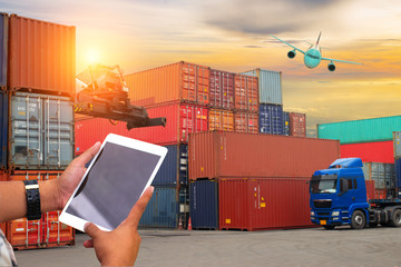 Young man hand holding blank screen tablet with logistic system (plane,cargo,truck,) import and exxport concept.