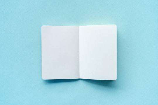 Empty notebook on plastel color background.