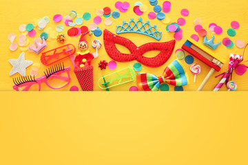 Party colorful noisemaker, mask and cute clown doll over yellow wooden background . Top view, flat lay Wall mural