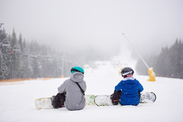 Back view of pair of snowboarders with boards on sitting on snow-covered slope in winter snowfalling weather. Couple looking at each other on wooded mountain hill. Fear, uncertainty, support concept