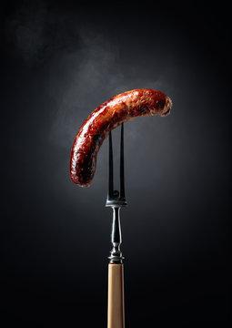 Grilled Bavarian sausage on a fork.