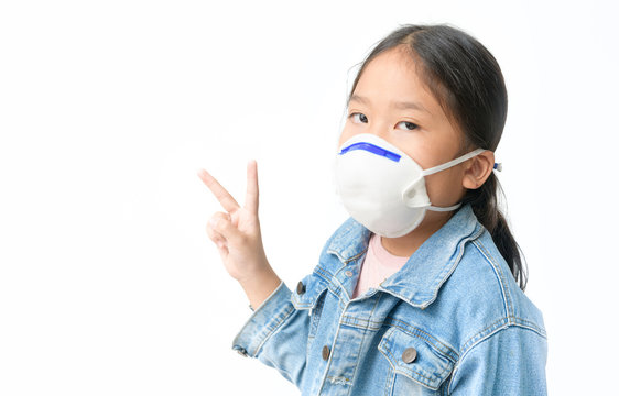 Asian girl wear N95 mask to protect PM 2.5 dust and show victory finger sign.