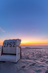 Beach chairs after sunset at the beach on Juist, East Frisian Islands, Germany.