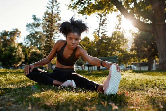 Portrait of a determined fitness young african american woman sitting on green grass doing exercise in the park - young black woman warming up her muscles before exercising