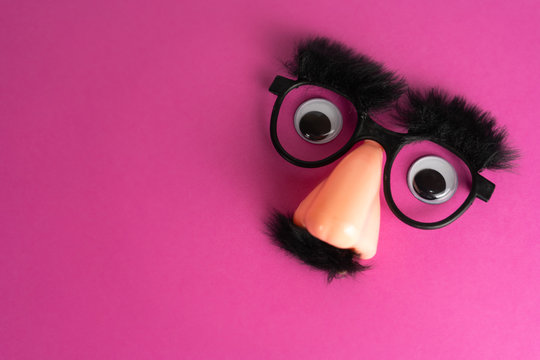 Funny face mask with big eyes and pink background with lot of copy space
