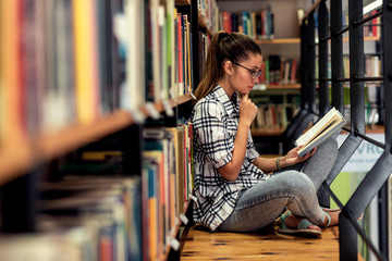 Young female student study in the library reading book while sitting near bookshelf.