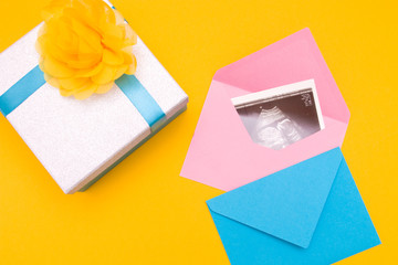 pic ultrasound in a pink envelope, box and a blue envelope with a blue ribbon and a yellow flower made of fabric, yellow background copy space top view, pregnancy by a girl, expecting a newborn