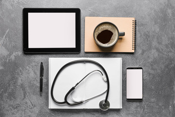 Stethoscope with tablet computer, mobile phone, notebooks and cup of coffee on dark background