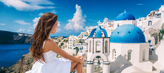 Travel Greece vacation luxury Europe cruise destination woman tourist panoramic of Santorini island. Asian lady in white dress looking at view of famous blue domes church panorama.