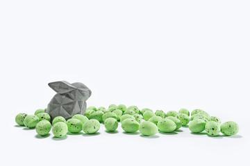 Deko Osterhase zwischen grünen Ostereiern