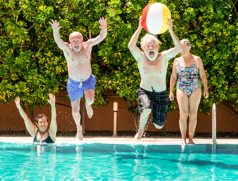 funny view of couples of senior people playing in the blue and transparent water of the swimming pool. Man jumps into the pool with a large inflatable ball