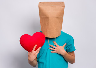 Fototapete - Valentines Day concept. Teen boy with paper bag over head holds red heart. Boy holding symbol of love, family, hope. Teenager cover head with bag posing in studio. Child pulling paper bag over head.