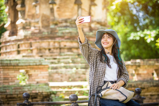 Tourist Asia woman with a backpack Walking and studying the history of the temple, taking photos of the ancient temples of the ancient temples of Thailand