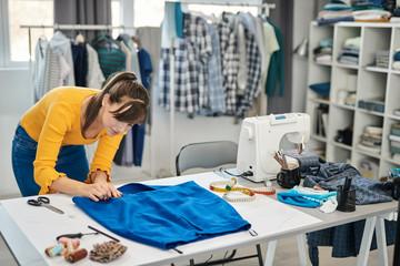Focused beautiful caucasian seamstress putting pin on seam and making beautiful skirt.