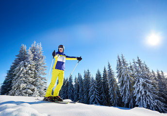 Young female posing in skis and goggles. Happy skier showing thumbs up with ski poles in hands. Fun day at ski resort during winter vacation. Dense coniferous forest under blue sunny sky on background