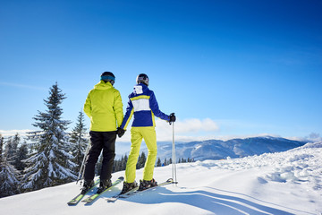 Couple of skiers holding hands on wooded mountain edge, enjoying wonderful beauty of nature at ski resort. Winter mountain panoramic landscape on background. Clear blue sky with copy space. Back view.