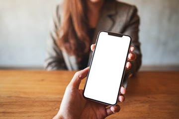 Mockup image of a woman holding and showing white mobile phone with blank black desktop screen to someone