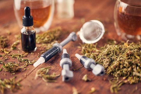Medical marijuana concept - Injection of CBD oil, CBD paste, dried marijuana leaves on wooden background