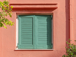 vibrant green shutters window on peach colored wall