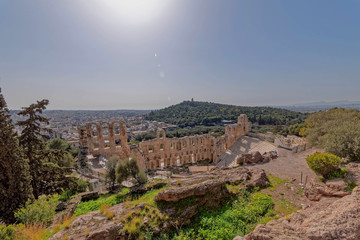 Greece, Herodium open odeon under Acropolis and Athens panoramic view under hot burning sun with light lens flare