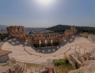 Greece, Herodium open odeon under Acropolis and Athens cityscape under hot burning sun with light lens flare