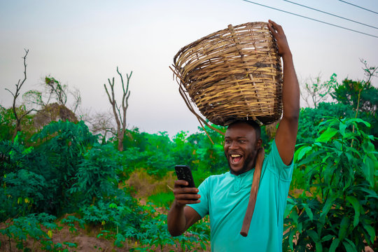 young black happy farmer carrying a basket of his farm produce on his head
