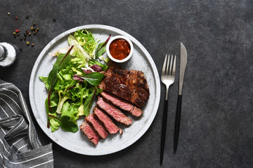 Poster de jardin Steakhouse Grilled marbled beef steak with salad in a plate on the kitchen table. With copy space under the text.