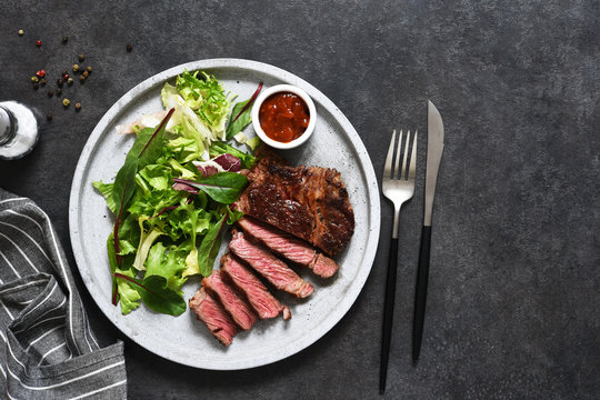Grilled marbled beef steak with salad in a plate on the kitchen table. With copy space under the text.