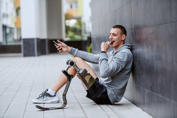 Fotomurales - Young attractive caucasian sportsman with artificial leg sitting on ground, leaning on wall, using smart phone and eating his chocolate bar.