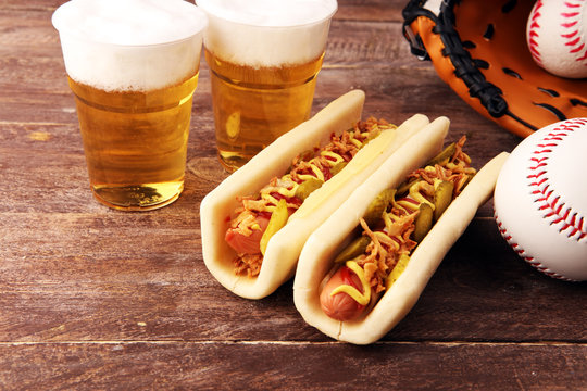 Grilled hot dogs with mustard and ketchup on the table with draft beer. Baseball party food with balls for the playoffs