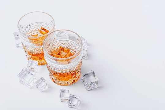 two glasses of whiskey with ice on a white background with place for text