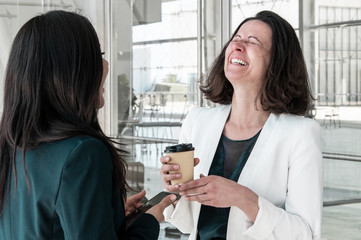 Business women talking, laughing and drinking coffee. One woman is standing back to camera in...